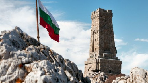 National memorial monument on Shipka peak, Bulgaria and waving Bulgarian flag
